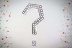Pillen in der Blisterpackung in Form eines Fragezeichens und in den Tabletten auf weißem Hintergrund Medizinisch, Gesundheitswese Stockbilder