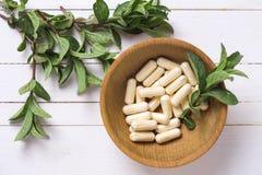 Pillen in der Schüssel und in den Blättern der Minze auf weißer Tabelle Stockfoto