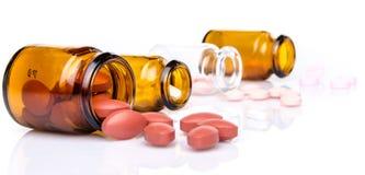 Pillen, die aus Pilleflasche heraus verschüttet werden Stockfotos