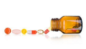 Pillen, die aus Pilleflasche heraus verschüttet werden Lizenzfreies Stockfoto