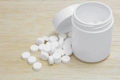 Pillen, die aus Tablettenfläschchen auf Holzrückseitenboden heraus verschüttet werden Stockbilder