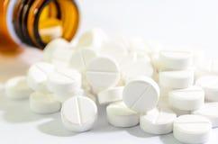 Pillen, die aus Tablettenfläschchen heraus verschüttet werden Stockfoto