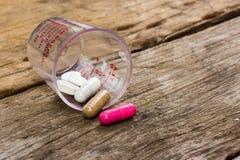 Pillen, die heraus auf alter Tabelle verschüttet werden Stockbilder