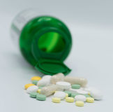 Pillen, die heraus eine grüne Flasche fallen Stockfoto