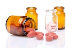 Pillen die uit pillenfles morsen Stock Afbeeldingen