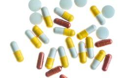 Pillen en capsules tegen witte terug aangestoken achtergrond stock fotografie