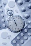Pillen en chronometer stock afbeeldingen
