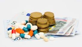 Pillen en geld royalty-vrije stock afbeelding