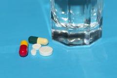 Pillen en Glas Water op blauwe achtergrond royalty-vrije stock foto's