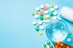 Pillen en glas water op blauwe hoogste mening royalty-vrije stock foto's