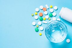 Pillen en glas water op blauwe hoogste mening royalty-vrije stock afbeeldingen