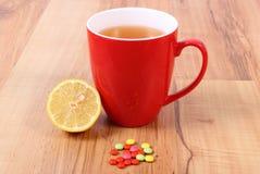 Pillen en hete thee met citroen voor koude, behandeling van griep en lopend Royalty-vrije Stock Afbeeldingen