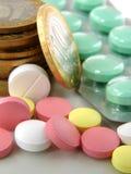 Pillen en muntstukken stock foto's