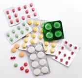 Pillen en tabletten die op witte achtergrond worden geïsoleerda Stock Foto