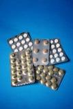 Pillen getrennt auf Blau Stockfotografie