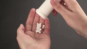 Pillen gossen in eine Hand von einem Glas stock footage