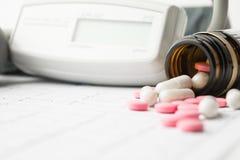 Pillen im dunklen Glas im Fokus und in der Ausrüstung für Blutdruck Stockfotos