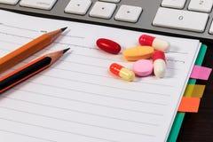 Pillen, Kapsel, Notizbuch, Bleistifte und Computertastatur auf Holztisch Stockfotos