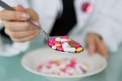 Pillen in lepel op witte schotel stock afbeelding