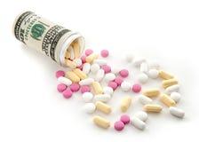 Pillen liefen eine Flasche über, die vom Geld hergestellt wurde Stockfotografie