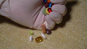 Pillen Medicijnclose-up De hand zet multicolored pillen en capsules op een servet Biologisch actieve Additieven en stock video