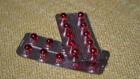 Pillen Medikationsnahaufnahme Blasen mit roten runden Kapseln liegen auf einer Serviette Biologisch-aktive Zusätze und Vitamine stock footage