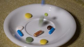Pillen Medikationsnahaufnahme Ein Stapel von mehrfarbigen Pillen fällt langsam auf eine weiße Platte Biologisch-aktiv stock video