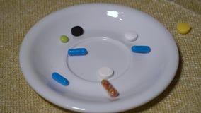 Pillen Medikationsnahaufnahme Ein Stapel von mehrfarbigen Pillen fällt langsam auf eine weiße Platte Biologisch-aktiv stock footage