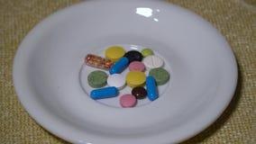 Pillen Medikationsnahaufnahme Ein Stapel von mehrfarbigen Tabletten liegt auf einer weißen Untertasse Biologisch-aktive Zusätze u stock footage