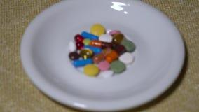 Pillen Medikationsnahaufnahme Ein Stapel von mehrfarbigen Tabletten liegt auf einer weißen Untertasse Biologisch-aktive Zusätze u stock video footage