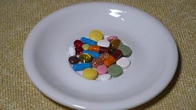 Pillen Medikationsnahaufnahme Ein Stapel von mehrfarbigen Tabletten liegt auf einer weißen Untertasse Biologisch-aktive Zusätze u stock video