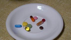 Pillen Medikationsnahaufnahme Nahaufnahmehand setzt mehrfarbige Pillen und Kapseln auf eine weiße Platte Biologisch-aktiv stock video