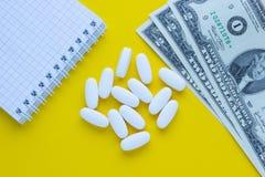 Pillen met een blocnote en een geld op een gele achtergrond stock afbeeldingen