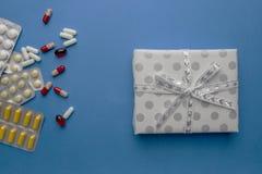 Pillen met giftdoos met boog op blauwe achtergrond stock foto