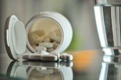 Pillen mit Tablettenfläschchen und Glas Wasser Lizenzfreie Stockfotos