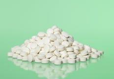 Pillen naar groene achtergrond Stock Fotografie
