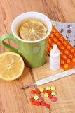 Pillen, neusdalingen en hete thee met citroen voor koude, behandeling van griep en lopend Stock Fotografie