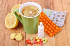 Pillen, neusdalingen en hete thee met citroen voor koude, behandeling van griep en lopend Royalty-vrije Stock Foto's
