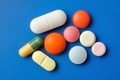 Pillen op Blauw Stock Afbeeldingen