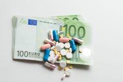 Pillen op euro geld dat op witte achtergrond wordt geïsoleerd Geneeskundeuitgaven Plaats voor tekst royalty-vrije stock foto