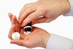 Pillen in oude man hand Stock Foto's