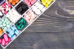 Pillen in plastic container op houten lijst Stock Foto's