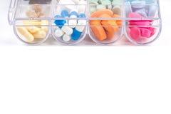 Pillen in plastic container op wit Stock Fotografie