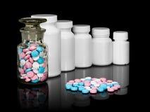 Kleine groep een pil tegen kleine flessen met pillen. Royalty-vrije Stock Afbeeldingen