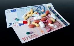 Pillen, tabletten en capsules op bankbiljetten worden uitgespreid dat Stock Fotografie