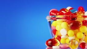 Pillen, Tabletten und Drogen, die auf Blau sich drehen stock footage