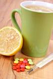 Pillen, thermometer en hete thee met citroen voor koude, behandeling van griep en lopend Royalty-vrije Stock Foto