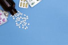 Pillen uit pillenfles worden gemorst met geneeskrachtige tabletten op blauwe achtergrond die stock foto
