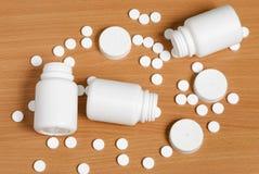 Pillen und Flaschen auf flacher Holzoberfläche Stockbild