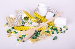 Pillen und messendes Band, hölzernes spoone, Konzeptdiät Stockfoto